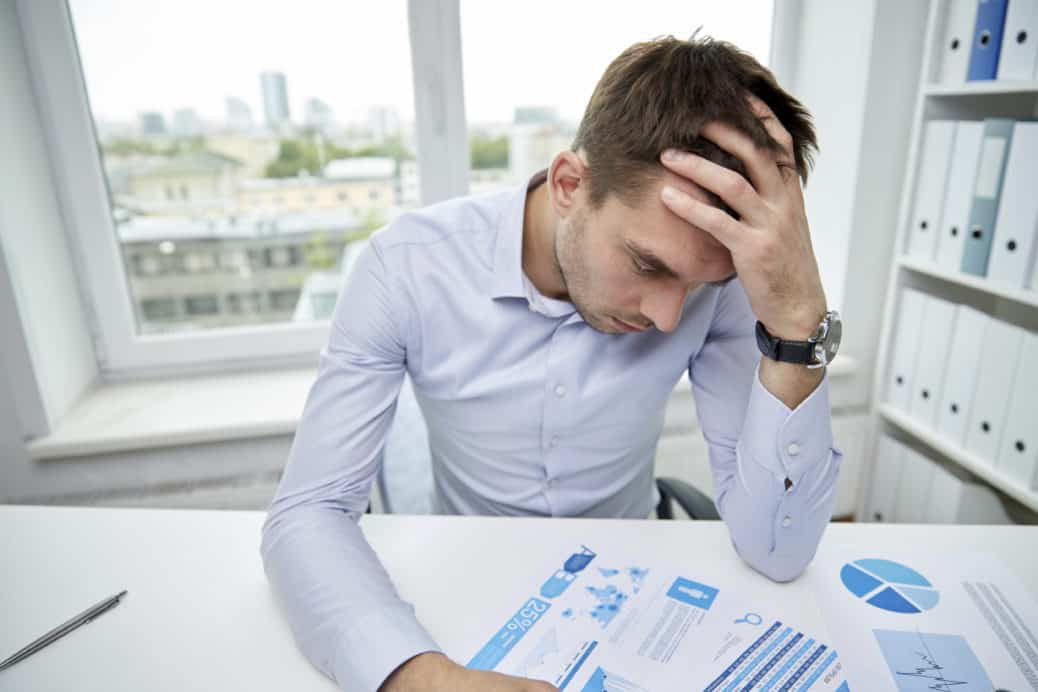 stressed businessman with papers in office